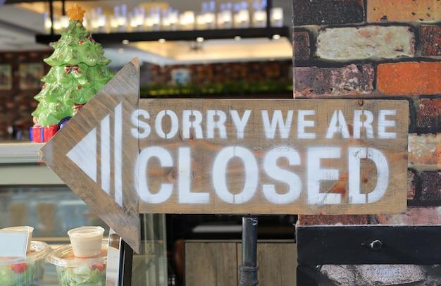 Sorry wij zijn gesloten teken op pijl houten bord Premium Foto
