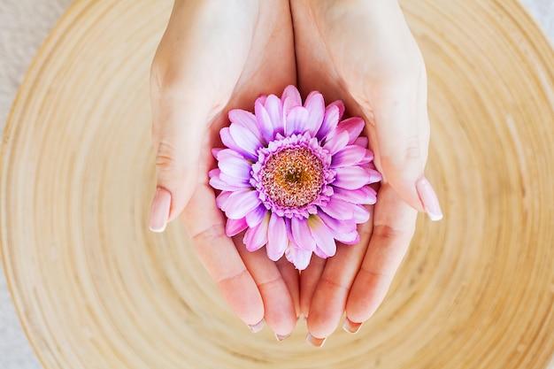 Spa behandelingen. vrouw houdt mooie bloem in haar handen Premium Foto