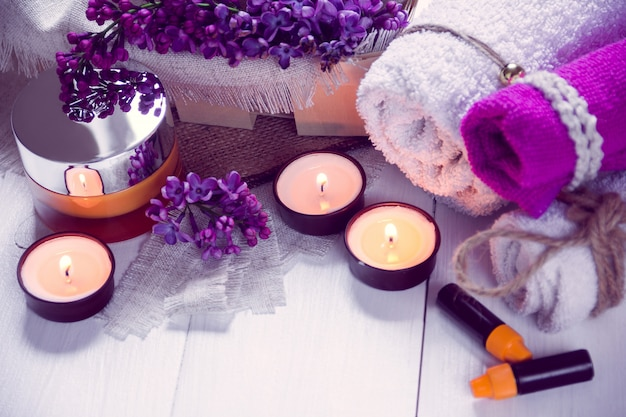 Spa bestaat uit handdoeken, lila, kaarsen, room en olie Premium Foto
