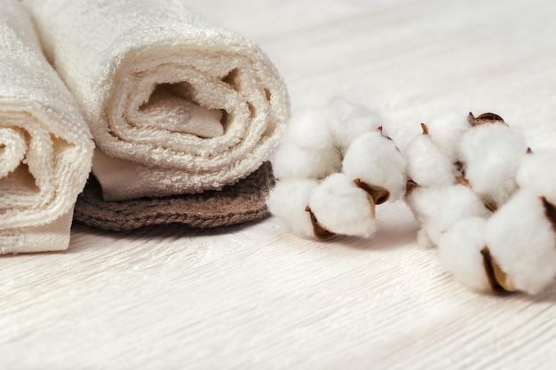 Spa concept. katoenen bloemplant en katoenen opgerolde handdoek. gestemde foto. Premium Foto