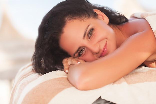 Spa en massage. de mooie vrouw krijgt gezicht en achtermassage op zonnig strand. van hoge kwaliteit. Premium Foto