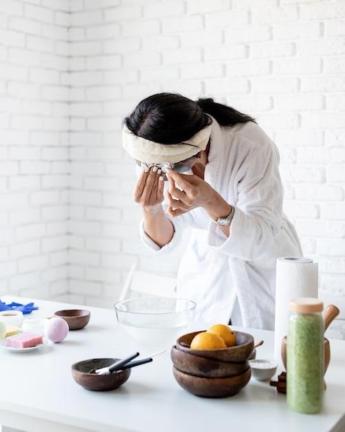 Spa- en wellness-concept. zelfzorg. portret van een vrouw in witte badjassen die gezichtsmasker maken die kuuroordprocedures doen Premium Foto