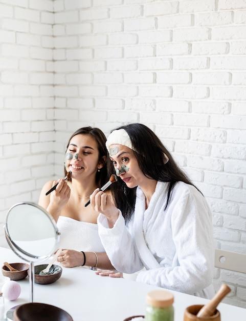Spa- en wellness-concept. zelfzorg. twee mooie vrouwen die gezichtsmasker met plezier toepassen Premium Foto