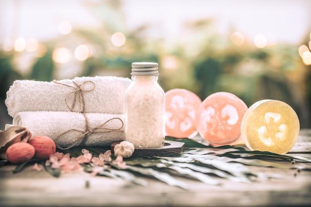 Spa handgemaakte zeep met witte handdoeken en zeezout, samenstelling op tropische bladeren, houten achtergrond Gratis Foto