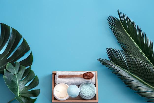 Spa. lichaamsverzorging op blauw met tropische bladeren. Gratis Foto