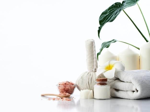 Spa massage concept, kruiden kompres bal, room, bloem zeep, geurkaars en himalaya roze zout, geïsoleerd Premium Foto