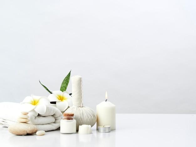 Spa massageconcept, kruidenkompres, crème, bloemenzeep, geurkaars Premium Foto