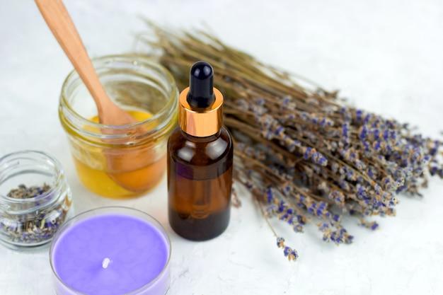 Spa-set met honing, lavendelolie, kaars en droge lavendel Premium Foto