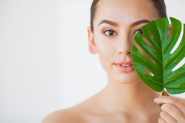 Spa zorg. jonge vrij donkerbruine vrouw met groot groen blad Premium Foto