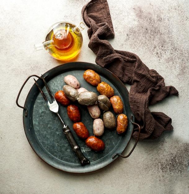 Spaans eten - spaanse worstjes op de snijplank - butifarra blanca, chorizo, morcilla de cebolla Premium Foto