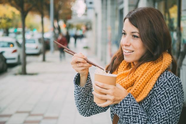 Spaans meisje dat de duwtjes neemt om in de straat te eten Premium Foto