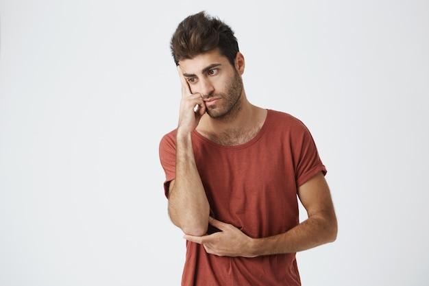 Spaanse ongeschoren knappe kerel in rode t-shirt knorrig het kijken opzij houdend hand op voorhoofd verstoord over ruzie met vriend. Gratis Foto