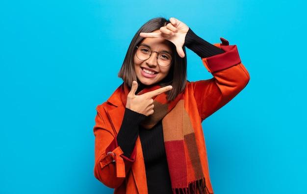 Spaanse vrouw voelt zich gelukkig, vriendelijk en positief, lacht en maakt een portret of fotolijst met handen Premium Foto