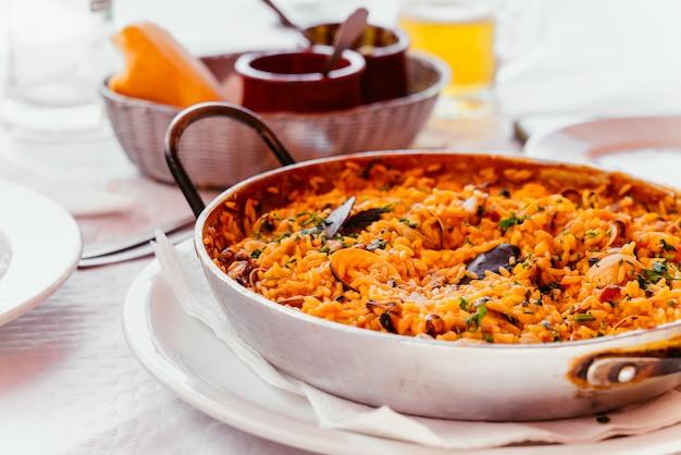 Spaanse zeevruchten paella met mosselen, garnalen etc. in een stalen paella pan. canarische eilanden keuken in een klein familierestaurant. Gratis Foto