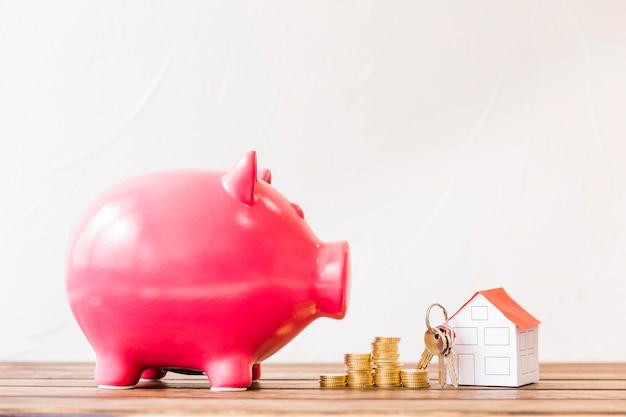Spaarpot dichtbij gestapelde muntstukken en huis met sleutel Gratis Foto