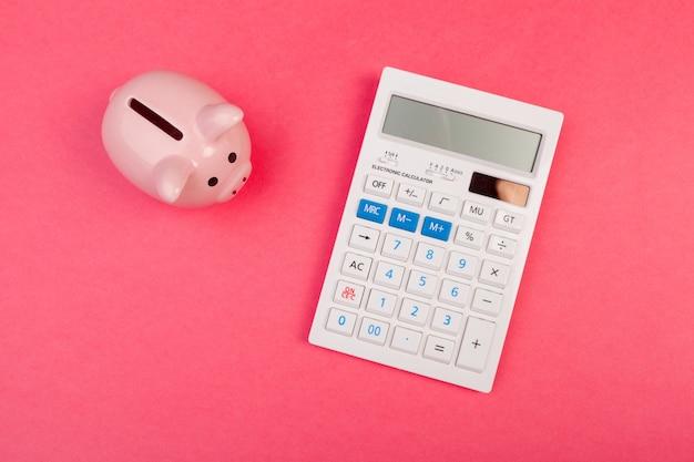Spaarvarken en calculator op kleurenachtergrond, hoogste mening. Premium Foto