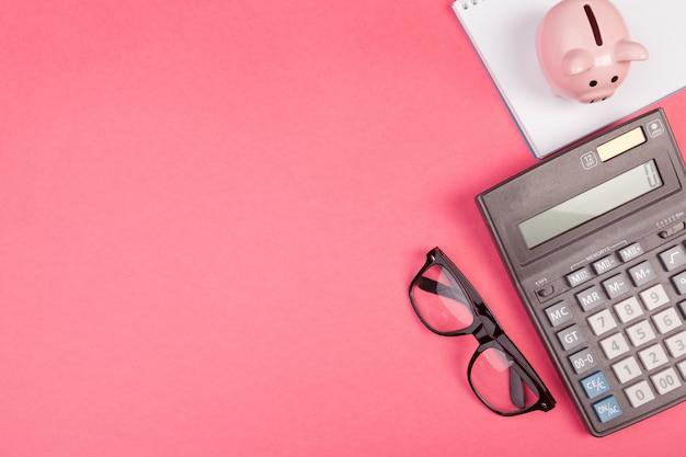 Spaarvarken en rekenmachine op kleur, bovenaanzicht, Premium Foto