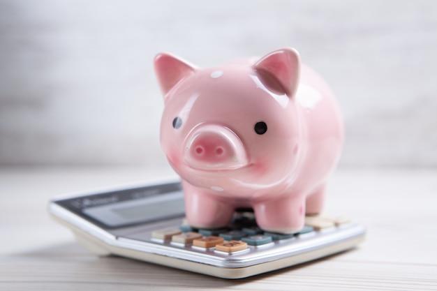 Spaarvarken met calculator op witte achtergrond Premium Foto