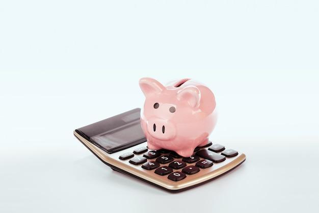Spaarvarken met geïsoleerde calculator Premium Foto