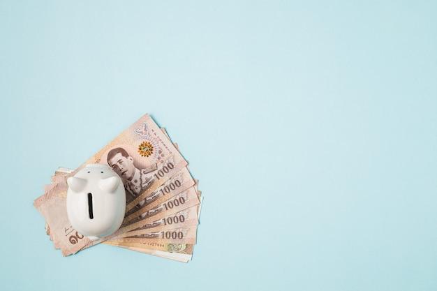 Spaarvarken met thaise munt, 1000 baht, geldbankbiljet van thailand op blauwe achtergrond voor zaken en financiënconcept opslaan Premium Foto