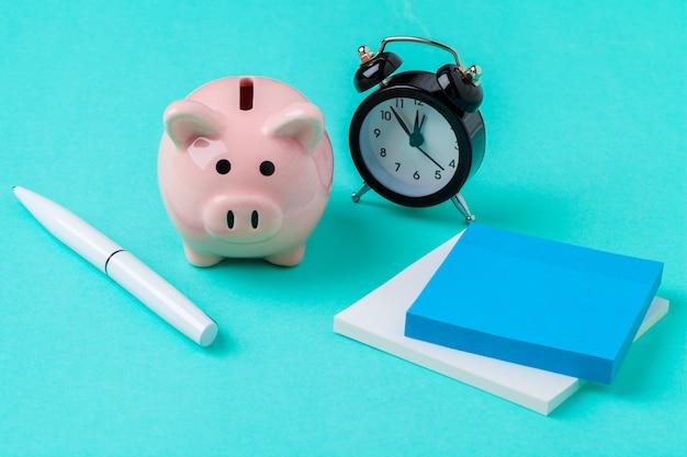 Spaarvarken sparen munt en wekker, tijd en geldconcept. Premium Foto