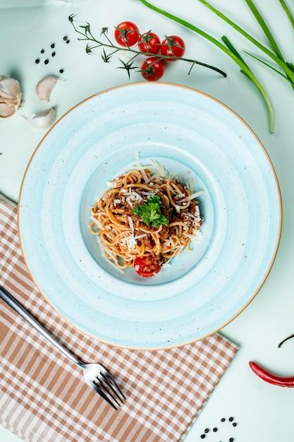 Spaghetti bolognese gegarneerd met kaas en kruiden Gratis Foto