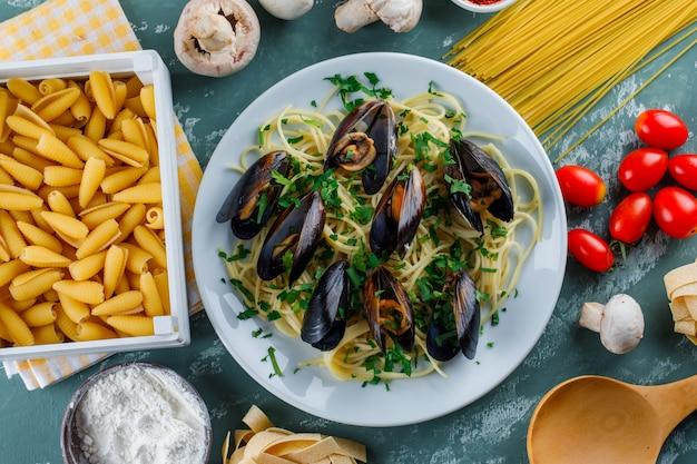 Spaghetti en mossel in een plaat met rauwe pasta, tomaat, meel, champignons, houten lepel Gratis Foto