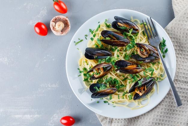 Spaghetti en mossel met tomaten, champignons, vork in een plaat op keukenpapier Gratis Foto