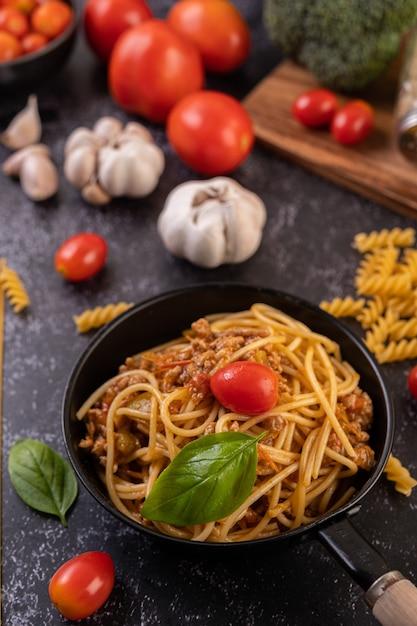 Spaghetti gebakken in een pan gebakken met tomaten en basilicum Gratis Foto