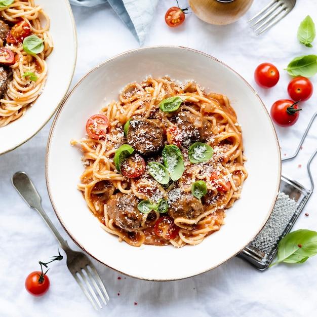 Spaghetti gehaktbal gegarneerd met parmezaan en basilicum food fotografie Gratis Foto
