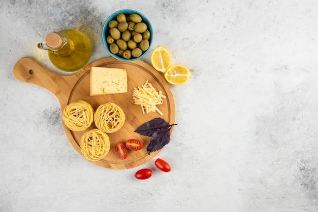 Spaghetti, groenten en kaas op een houten bord met olijven. Gratis Foto
