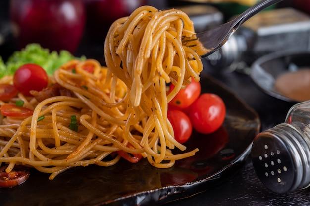 Spaghetti in een zwarte kop met tomaten en sla. Gratis Foto