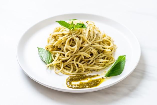 Spaghetti met pestosaus, olijfolie en basilicumbladeren. Premium Foto