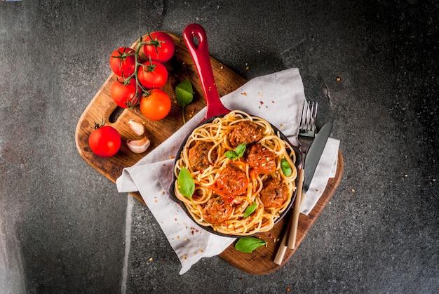 Spaghetti pasta met gehaktballetjes, basilicum tomatensaus in rode gietijzeren pan, op zwarte stenen tafel met snijplank Premium Foto