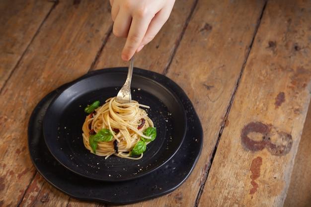 Spaghetti pasta met groenten, peper, basilicum bladeren op zwarte ronde plaat op bruin rustieke vintage houten achtergrond Premium Foto