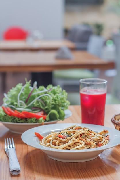 Spaghettischotel met wokgroenten en verse salade in een restaurant. detailopname. Premium Foto