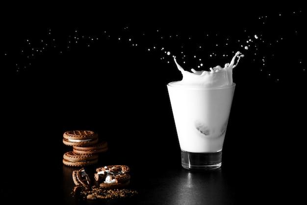 Spalsh in glas melk en chocoladekoekjes op zwarte Premium Foto