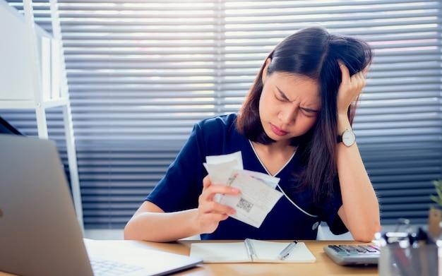 Spanning gezicht aziatische vrouw hand met onkostenrekening en berekening over schuldrekeningen maandelijks aan de tafel in het kantoor aan huis. Premium Foto