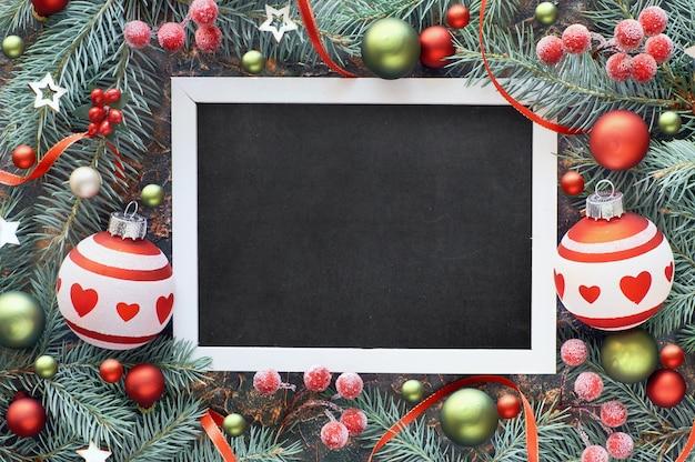 Spartakje versierd met kerstballen, bessen en sterren, zwart bord Premium Foto