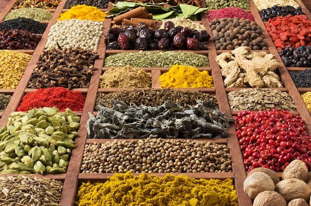 Specerijen en kruiden in houten trays, bovenaanzicht. kruiderijen voor het bereiden van heerlijk eten. Premium Foto