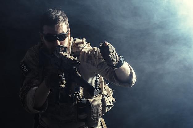 Special forces soldaat met geweer op donker Premium Foto