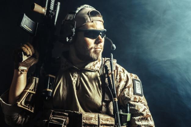 Speciale troepenmilitair met geweer op dark Premium Foto