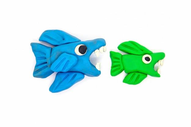 Speel deeg grote vissen eten kleine vissen op wit Premium Foto
