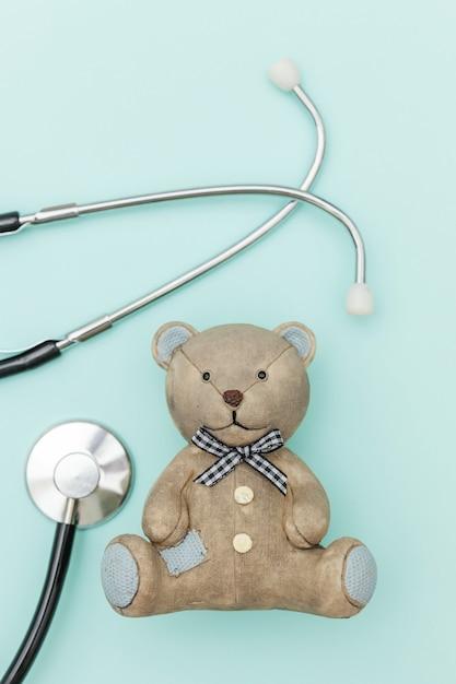 Speelgoed beer en geneeskunde apparatuur stethoscoop geïsoleerd op pastel blauwe achtergrond Premium Foto