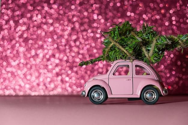 Speelgoed model auto met kerstboom op het dak rijdt op roze blurred glitter achtergrond Premium Foto