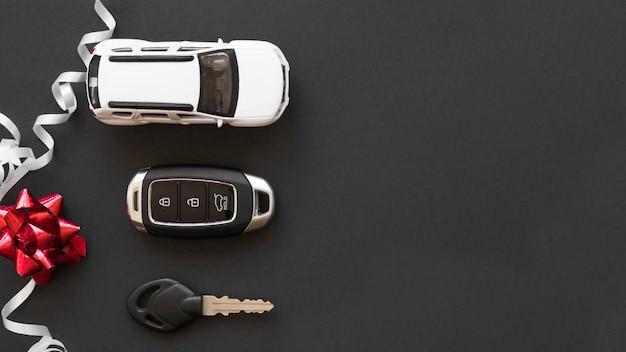 Speelgoedauto dichtbij alarmsleutels en boog Gratis Foto