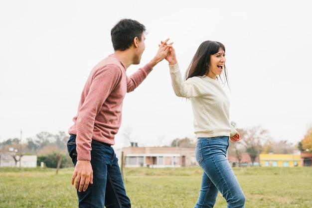 Speels jong paar dat holdingshanden loopt Gratis Foto