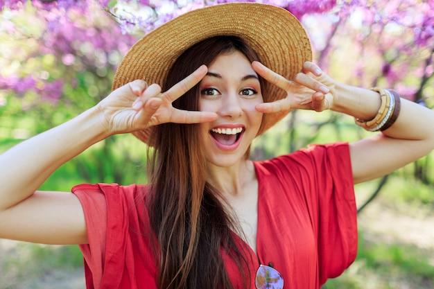Speels schattig meisje grappig gezicht maken en tekenen, poseren in voorjaar park op bloeiende bomen Gratis Foto