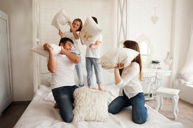 Speelse familie die grappig hoofdkussengevecht op bed heeft Gratis Foto