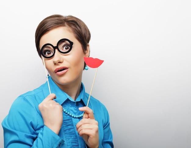 Speelse jonge vrouw met lippen en glazen op een stokje Premium Foto
